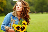 Young fashion woman with a bouquet of sunflowers in the field — Stock Photo