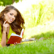 Beautiful girl with book in the autumn park — Stock Photo #30129873