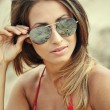 Young beautiful woman in red bikini and sunglasses at beach — Stock Photo