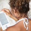 Woman with an e-reader on vacation at the beach reading a book.  — Stock Photo