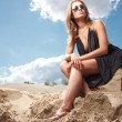 Stock Photo: Young womin black dress siting on sand