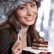 Beautiful winter woman eating cake — Stock Photo