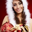 Winter portrait of a beautiful young smiling woman with a gift i — Stock Photo