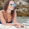 Young happy woman in black bikini on beach — Stockfoto