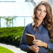 Businesswoman standing outside a modern house — Stock Photo #31918813