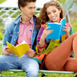Couple of students sitting outdoors studying and smiling — Stock Photo