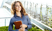 Beautiful young businesswoman among the skyscrapers of the moder — Stock Photo