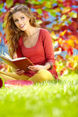 Portrait of a gorgeous brunette woman reading a book in the autu — Stok fotoğraf