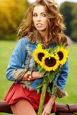 Mujer joven con un ramo de girasoles en el campo — Foto de Stock