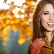Young woman with autumn leaves in hand and fall yellow maple gar — Stock Photo #32376779
