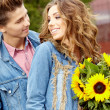 Loving young man hugging his girlfriend with sunflowers in their — Stock Photo