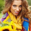 Young fashion woman with a bouquet of sunflowers in the field — Stock Photo #33255373