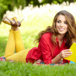 Beautiful student reading and relaxing in park  — Stok fotoğraf
