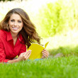 Young beautiful woman lays on green field and reads book.  — Stock Photo