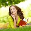 Beautiful student reading and relaxing in park — Stock Photo