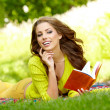 Beautiful student reading and relaxing in park — Stock Photo #33317253