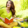 Young beautiful woman lays on green field and reads book. — Stock Photo #33317255