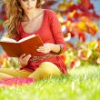 Brunette girl reading a book in the park — Stock Photo