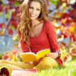 Brunette girl reading a book in the park — Stock Photo #33317373