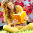 Portrait of a gorgeous brunette woman reading a book in the autu — Stock Photo