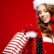 Sexy santa woman holding colorful shopping bags — Stock Photo #33750473