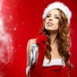 Winter portrait of a santa woman with a christmas gift — Stock Photo #33750417