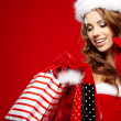 Stock Photo: Sexy santa woman holding colorful shopping bags