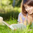 Female student lying on the grass with a books — Stock Photo
