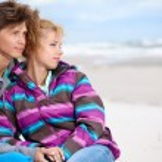 Couple embracing on coast behind blue sky — Stock Photo