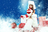 Santa woman with a christmas gift — Stockfoto