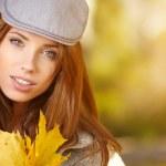Woman smiling joyful and blissful holding autumn leaves — Stock Photo