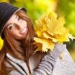 Womsmiling joyful and blissful holding autumn leaves — Stock Photo #34344381