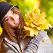 Woman smiling joyful and blissful holding autumn leaves — Stock Photo