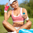 Young sporty woman drinking water from a bottle in a park — Stock Photo