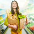Stock Photo: Young womholding grocery bag full of bread