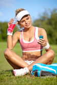 Young sporty woman drinking water from a bottle in a park — Stockfoto