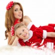 Stock Photo: Beautiful woman and little girl dressed in costume santa claus