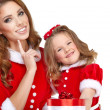 Woman and little girl wearing santa claus costume — Stock Photo