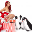 Christmas Girl in dress holding a large toy penquin. Shot in stu — Stock Photo