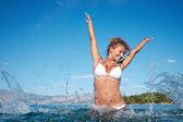 Woman in the sea splashing water — Stock Photo