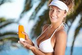 女孩抱着橘黄色的太阳晒乳液瓶. — 图库照片