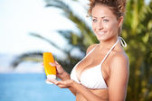 Girl holding orange sun tan lotion bottle. — Стоковое фото