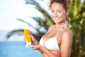 Girl holding orange sun tan lotion bottle. — Stock Photo