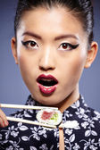 Asian woman eating sushi — Stock Photo