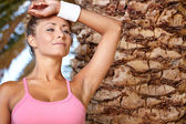 Fitness woman under palm in resort — Stock Photo