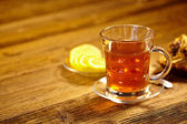 Glass of hot tea on rustic wooden table. — Stock fotografie