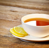 Cup of tea with lemon on the wooden table — Stockfoto