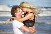 Couple in love on the beach flirting — Stock Photo