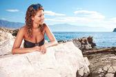 Bikini model posing against a setting sun — Foto Stock