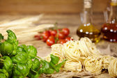 Vine tomatoes, basil, spaghetti — Stock Photo